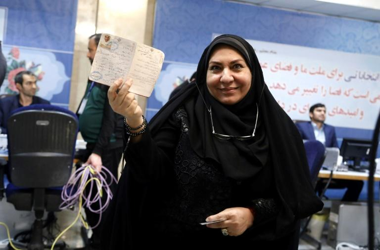 An Iranian woman shows her I.D at the interior ministry's election headquarters as candidates begin to sign up for next month's presidential elections in Tehran on April 11, 2017