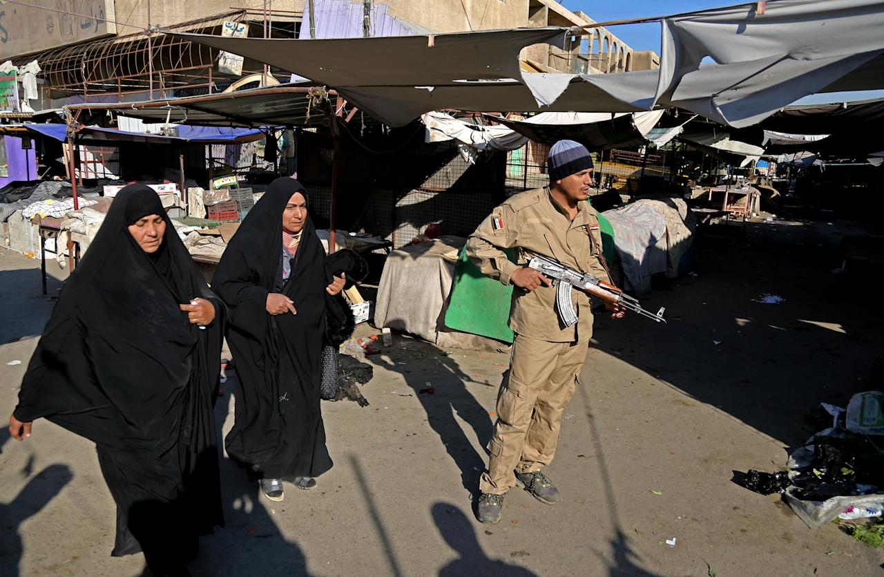An awakening council member stands guard while women walk through the site of a bombing in a Christian section of Baghdad, Iraq, Wednesday, Dec. 25, 2013. Militants in Iraq targeted Christians in two separate bomb attacks in Baghdad, officials said. The Christmas Day attacks brought the total number of people killed so far this month in Iraq to 441. According to U.N. estimates, more than 8,000 people have been killed since the start of the year. (AP Photo/Karim Kadim)