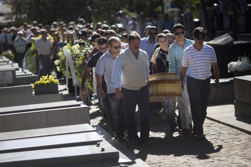 Relatives and friends carry the coffins of two brothers, Pedro and Marcelo Salla, who died in a nightclub fire, as they prepare to bury them at a cemetery in Santa Maria, Brazil, Monday, Jan. 28, 2013. Brazilian police officials said Monday they've made three detentions and are seeking a fourth person in connection with blaze that ripped through a nightclub in southern Brazil over the weekend, killing more than 230 people. (AP Photo/Felipe Dana)