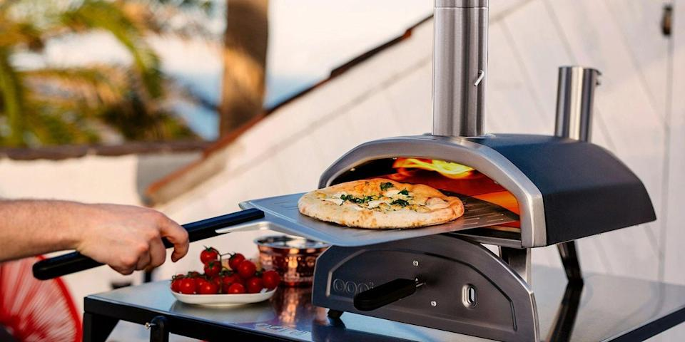 """<p>Cooking homemade pizzas in a wood-fired oven from the comfort of your home's backyard may seem like a pipe dream, but it's actually more attainable than you think it is. The outdoor pizza oven space used to just contain traditional models made from brick and high-heat mortar that run between $1,500 and $4,500. Luckily, today's outdoor ovens are mostly countertop models that are much more portable, versatile, and affordable than their traditional wood-burning counterparts. But they still help you serve that deliciously crispy and charred Neapolitan pizza you crave.</p><p>If you're determined to learn how to create the perfect pizza at home, we've found the best outdoor pizza ovens that you can purchase today.</p><h3 class=""""body-h3"""">The Best Outdoor Pizza Ovens</h3><ul><li><strong>Best Overall: </strong><a href=""""https://go.redirectingat.com?id=74968X1596630&url=https%3A%2F%2Fooni.com%2Fproducts%2Fooni-koda-16%3Fsscid%3D51k5_xc7q6&sref=https%3A%2F%2Fwww.bestproducts.com%2Fappliances%2Flarge-appliances%2Fg36546606%2Fbest-outdoor-pizza-ovens%2F"""" rel=""""nofollow noopener"""" target=""""_blank"""" data-ylk=""""slk:Ooni Koda 16 Outdoor Pizza Oven"""" class=""""link rapid-noclick-resp"""">Ooni Koda 16 Outdoor Pizza Oven</a></li><li><strong>Easiest to Use:</strong> <a href=""""https://go.redirectingat.com?id=74968X1596630&url=https%3A%2F%2Fooni.com%2Fproducts%2Fooni-koda%3Fsscid%3D51k5_xc7xq&sref=https%3A%2F%2Fwww.bestproducts.com%2Fappliances%2Flarge-appliances%2Fg36546606%2Fbest-outdoor-pizza-ovens%2F"""" rel=""""nofollow noopener"""" target=""""_blank"""" data-ylk=""""slk:Ooni Koda 12 Outdoor Pizza Oven"""" class=""""link rapid-noclick-resp"""">Ooni Koda 12 Outdoor Pizza Oven</a></li><li><strong>Best Budget Gas Oven: </strong><a href=""""https://www.amazon.com/dp/B07DYJZV6D?linkCode=ogi&tag=syn-yahoo-20&ascsubtag=%5Bartid%7C2089.g.36546606%5Bsrc%7Cyahoo-us"""" rel=""""nofollow noopener"""" target=""""_blank"""" data-ylk=""""slk:BakerStone Original Series Portable Gas Pizza Oven Box"""" class=""""link rapid-noclick-resp"""">BakerStone Original Series P"""