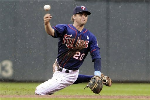 Minnesota Twins shortstop Brian Dozier throws out Milwaukee Brewers' Corey Hart after fielding a ground ball in the fifth inning of a baseball game, Sunday, June 17, 2012, in Minneapolis. (AP Photo/Jim Mone)