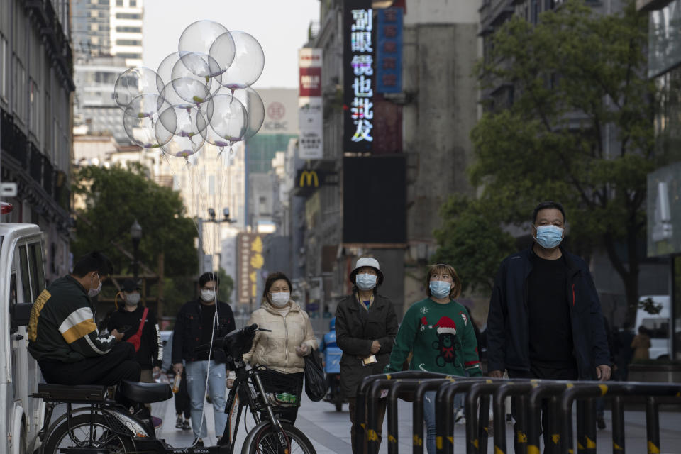 Residents wearing mask against the coronavirus walk through a partially closed retail street in Wuhan in central China's Hubei province on April 13, 2020. (AP Photo/Ng Han Guan)