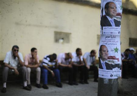 Egyptians sit on a bench near electoral posters of presidential candidate and former army chief Abdel Fattah al-Sisi as they wait for a polling station to open during the Egyptian presidential election near the Ittihadiya Palace in Cairo May 26, 2014. REUTERS/Amr Abdallah Dalsh