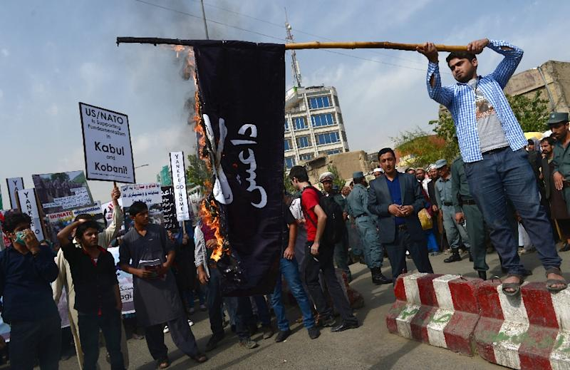 Afghan Solidarity members burn an Islamic State flag during a rally against the IS group in Kabul on October 12, 2014
