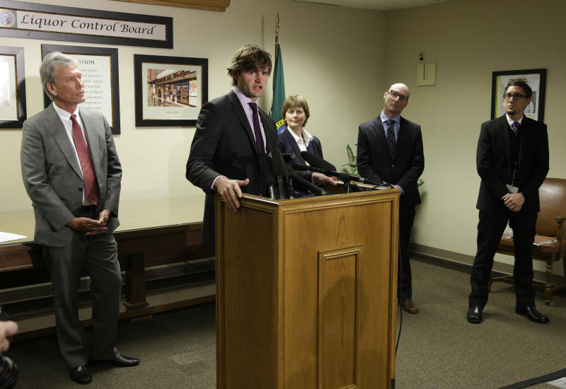 Steven Davenport, second from left, project manager for Botec Analysis Corp., takes questions from reporters Tuesday, March 19, 2013, as he is introduced in Olympia, Wash., along with other members of the team who are the tentative winners of the bidding process to be the official legal marijuana consultants for Washington State. Other team members are Michael Sautman, left, Lowry Heussler, third from right, David Lampach, second from right, and Beau Kilmer, right. Botec will advise Washington state officials as they develop rules for the state's new industry in legal, taxed marijuana. (AP Photo/Ted S. Warren)