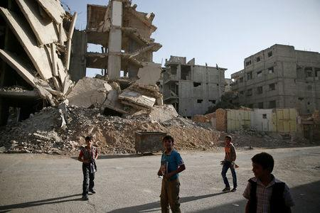 Boys walk near damaged buildings in the rebel-held besieged town of Zamalka, in the Damascus suburbs