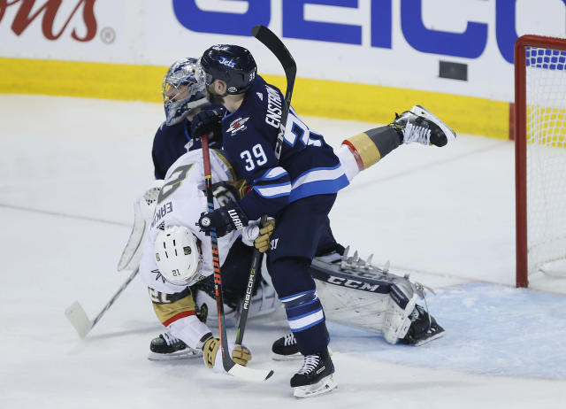 Winnipeg Jets' Toby Enstrom (39) takes Vegas Golden Knights' Cody Eakin (21) out of the play in front of goaltender Connor Hellebuyck (37) during the third period of Game 1 of the NHL hockey playoffs Western Conference finals, Saturday, May 12, 2108, in Winnipeg, Manitoba. (John Woods/The Canadian Press via AP)