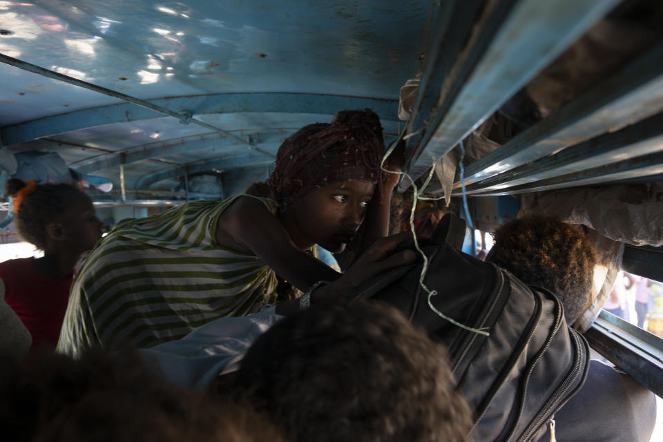 Refugees who fled the conflict in Ethiopia's Tigray region ride a bus going to the Village 8 temporary shelter, near the Sudan-Ethiopia border, in Hamdayet, eastern Sudan, Tuesday, Dec. 1, 2020. (AP Photo/Nariman El-Mofty)