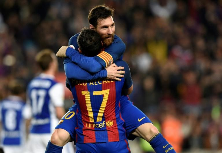 Barcelona's Paco Alcacer (bottom) celebrates with teammate Lionel Messi during their match against Real Sociedad at the Camp Nou stadium in Barcelona on April 15, 2017