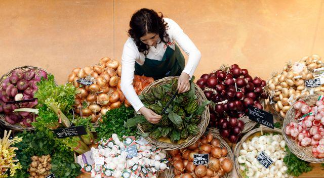 An employee arranges pricetags at a vegetables work bench during the opening day of upmarket Italian food hall chain Eataly's flagship store in downtown Milan