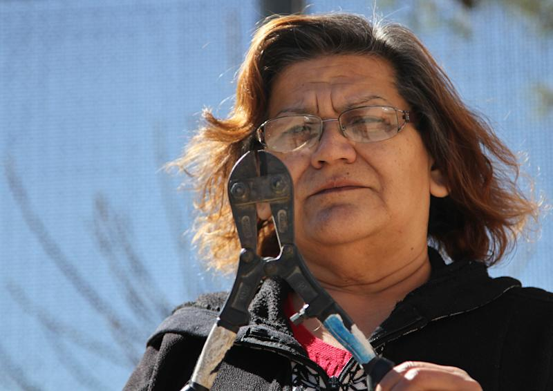 In this Tuesday, Feb. 12, 2013 photo, Patricia Rayjosa holds a pair of wire cutters left by border crossers she found in her backyard years ago at her home in El Paso, Texas. Like many residents of neighborhoods along the U.S.- Mexico border, Rayjosa remembers a time when immigrants would cross the border in droves and break into people's backyards and homes trying to hide from the Border Patrol. (AP Photo/Juan Carlos Llorca)
