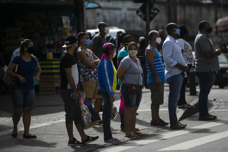 RIO DE JANEIRO, BRAZIL - MAY 08: Pedestrians wait to cross a street wearing face masks during the partial lockdown in the Campo Grande neighborhood on May 08, 2020 in Rio de Janeiro, Brazil. Campo Grande is the neighborhood with the highest number of complaints of crowding during the quarantine and the second with the most deaths from coronavirus (COVID -19) in the city of Rio de Janeiro according to City Hall. According to the Brazilian Health Ministry, Brazil has 135,106 positive cases of coronavirus (COVID-19) and a total of 9,146 deaths. (Photo by Bruna Prado/Getty Images)