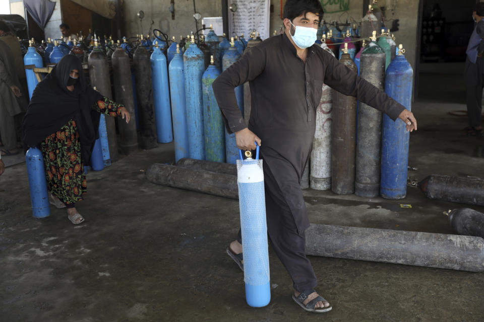 A man and woman carry an oxygen cylinders from a privately owned oxygen factory, in Kabul, Afghanistan, Saturday, June 19, 2021. Health officials say Afghanistan is fast running out of oxygen as a deadly third surge of COVID worsen. (AP Photo/Rahmat Gul)
