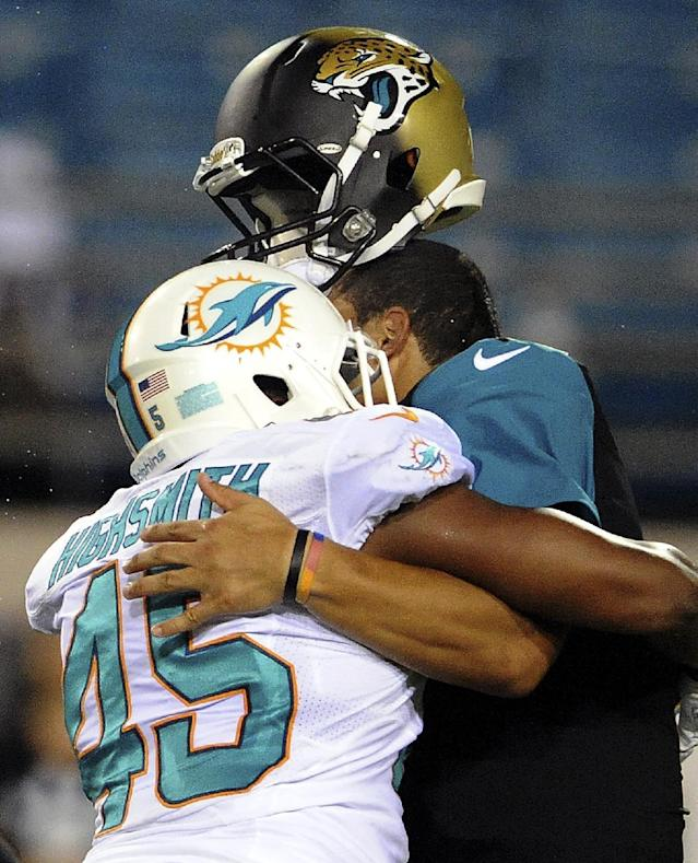 FILE - In this Aug. 9, 2013, file photo, Jacksonville Jaguars quarterback Matt Scott (5) has his helmet knocked off by Miami Dolphins outside linebacker Alonzo Highsmith (45) during the second half of an NFL preseason football game in Jacksonville, Fla. Highsmith was penalized for roughing the passer on the play. Almost once a game, an NFL player absorbs an illegal blow to the head or neck that could put his career, or worse, at risk. The NFL has been trying to prevent such blows over the past four years, targeting improper technique and making it a point of emphasis to penalize and fine players for hits that leave themselves and their opponents vulnerable. (AP Photo/Stephen Morton, File)