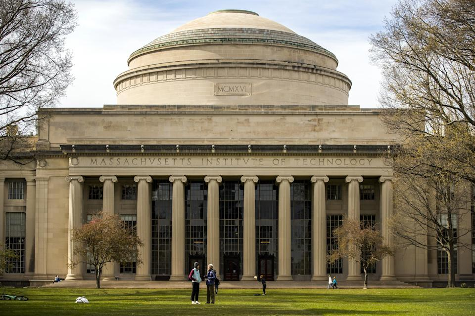 People stand on the lawn outside Building 10 on the Massachusetts Institute of Technology (MIT) campus in Cambridge, Mass. on Monday, April 20, 2020. (Adam Glanzman/Bloomberg via Getty Images)