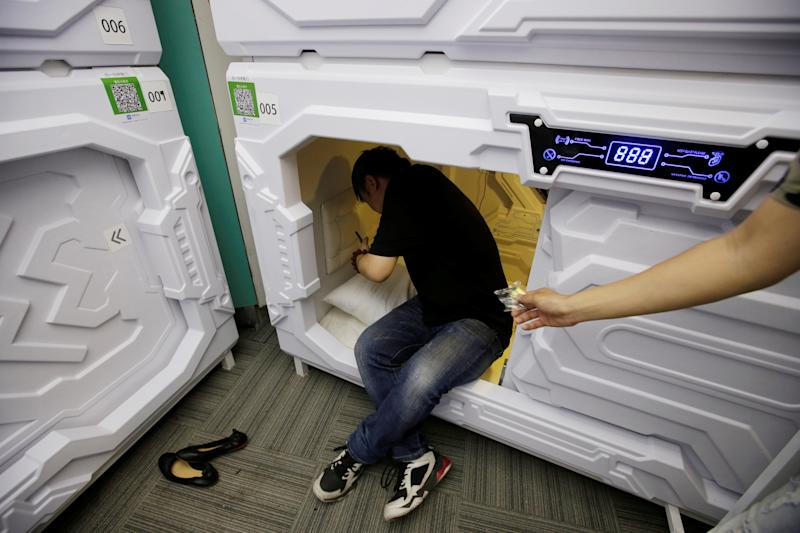 A staff member gives mute earplugs to a customer as he prepares to sleep in a capsule bed unit at Xiangshui Space during lunch break in Beijing's Zhongguancun area, China July 11, 2017. REUTERS/Jason Lee