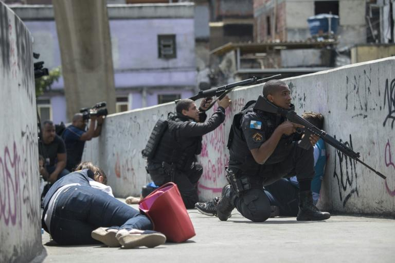 Policemen and journalists take cover during an operation to fight heavily armed drug traffickers at the Rocinha favela in Rio de Janeiro