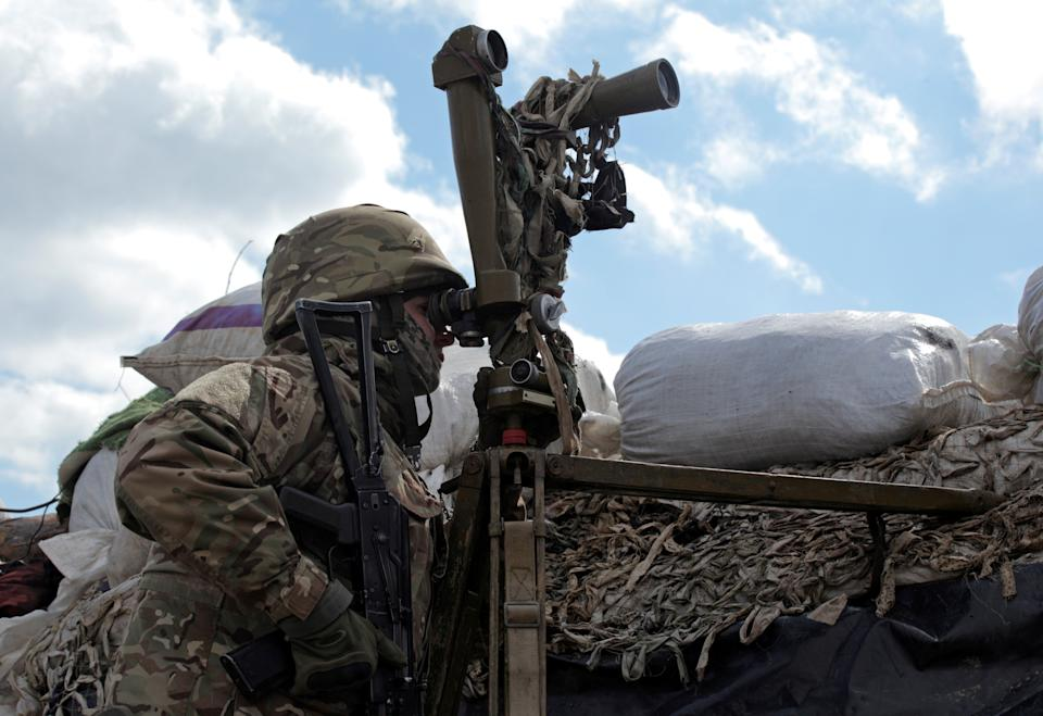 A service member of the Ukrainian armed forces uses periscopes while observing the area at fighting positions on the line of separation near the rebel-controlled city of Donetsk, Ukraine.
