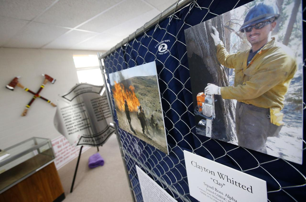 Artifacts and photographs honor the 19 Granite Mountain Hotshots killed nearly a year ago fighting a wildfire as part of a memorial exhibit being to mark the year anniversary of their deaths on Tuesday, June 24, 2014, in Prescott, Ariz. (AP Photo/Ross D. Franklin)
