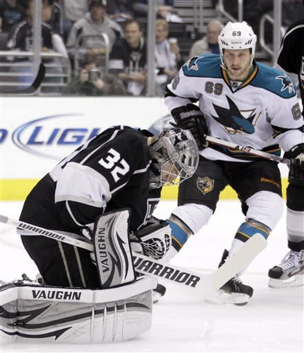 Los Angeles Kings goalie Jonathan Quick, left, stops a shot as San Jose Sharks center Andrew Desjardins looks on during the first period of an NHL hockey game in Los Angeles, Tuesday, March 20, 2012. (AP Photo/Jae C. Hong)