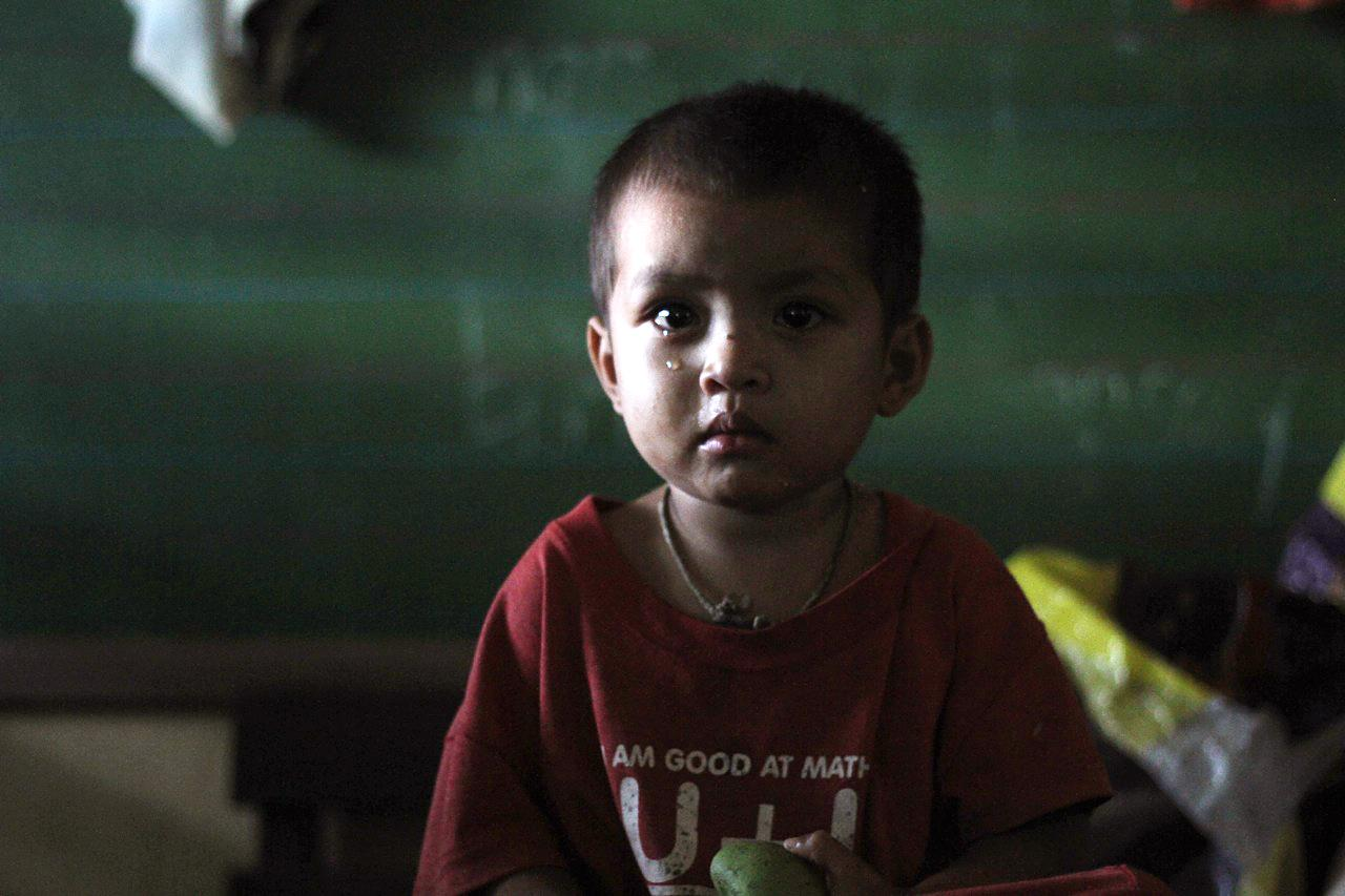 A boy waits in a temporary shelter after Typhoon Bopha made landfall in Compostela Valley in southeastern Philippines Tuesday Dec. 4, 2012. Typhoon Bopha (local name Pablo), one of the strongest typhoons to hit the Philippines this year, barreled across the country's south on Tuesday, killing at least 40 people and forcing more than 50,000 to flee from inundated villages. (AP Photo/Karlos Manlupig)
