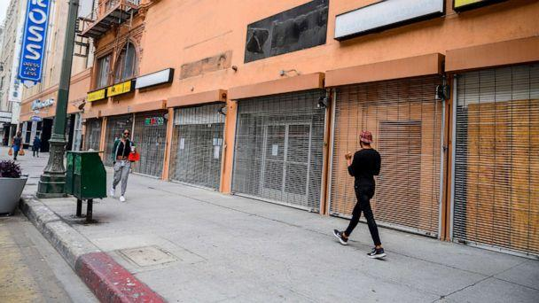PHOTO: In this April 30, 2020, file photo, people walk past closed shops in downtown Los Angeles. (Robyn Beck/AFP via Getty Images, FILE)