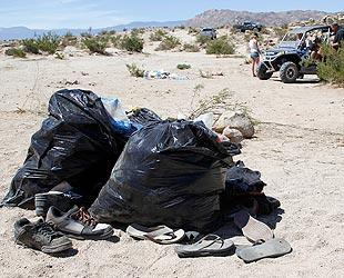 Trash bags sit on the sand after an off-road truck went out of control and ran into a crowd of spectators at the California 200