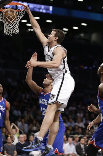 Brooklyn Nets forward Kris Humphries (43) dunks over Philadelphia 76ers forward Evan Turner (12) in the first half of an NBA basketball game, Tuesday, April 9, 2013, in New York. (AP Photo/Kathy Willens)
