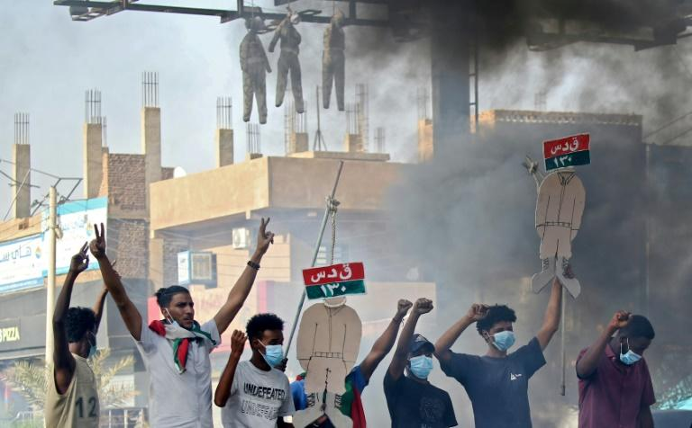 Sudanese protesters hang up effigies depicting Rapid Support Forces soldiers on the first anniversary of a deadly raid on an anti-government sit-in protest