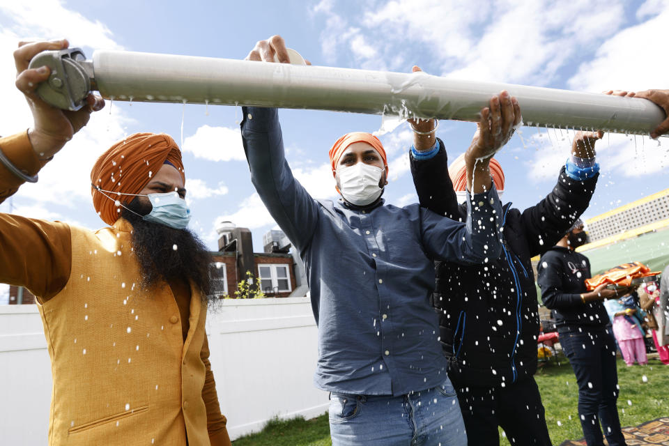 Jasbir Singh, left, and Vijay Singh wash a flagpole with milk as part of a ceremonial changing of the Sikh flag during Vaisakhi celebrations at Guru Nanak Darbar of Long Island, Tuesday, April 13, 2021 in Hicksville, N.Y. Sikhs across the United States are holding toned-down Vaisakhi celebrations this week, joining people of other faiths in observing major holidays cautiously this spring as COVID-19 keeps an uneven hold on the country. (AP Photo/Jason DeCrow)