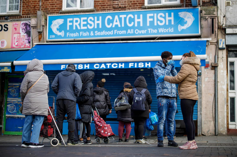 Image: People line up outside a local fishmongers before opening in Walthamstow, east London (Tolga Akmen / AFP - Getty Images)