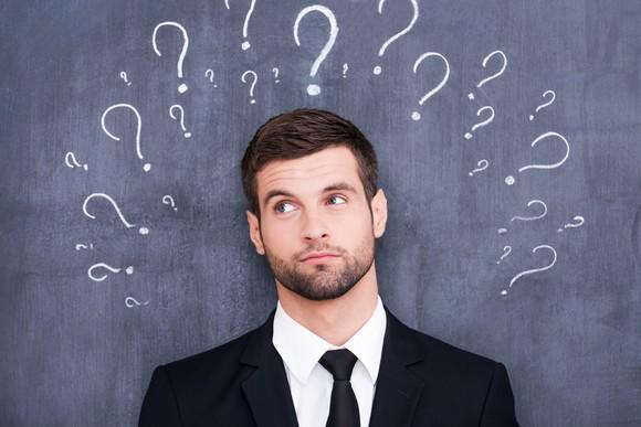 Man standing in front of chalkboard on which are drawn questions marks.