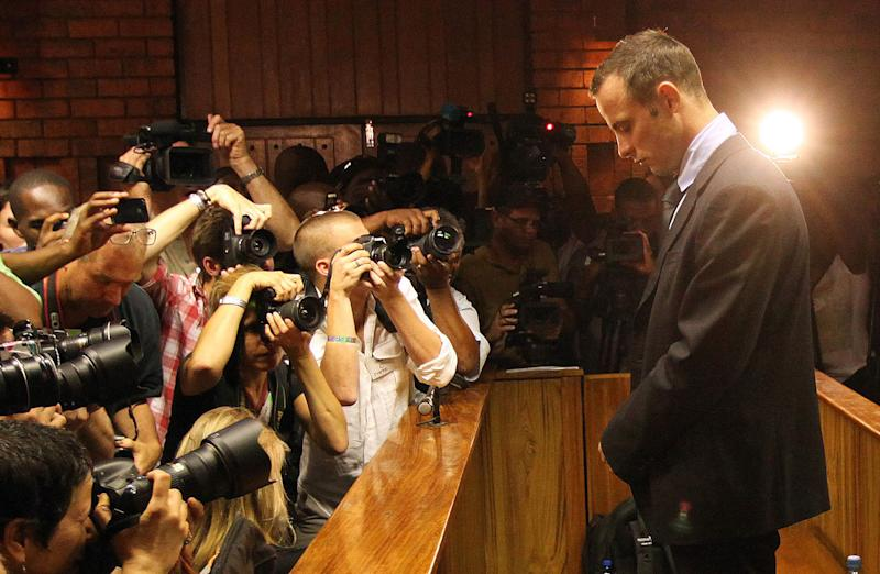 File: In this photo taken Friday, Feb. 22, 2013 photographers take photos of Olympic athlete Oscar Pistorius as he stands in the dock during his bail hearing at the magistrates court in Pretoria, South Africa. South Africa's police commissioner office said Tuesday Aug. 13, 2013 that Oscar Pistorius will be served with an indictment next week after police completed an investigation into the shooting death of his girlfriend. On Monday August 19, the accused,Oscar Pistorius, will appear on court in Pretroia. It is expected that he will be served with an indictment and that the matter will be postponed. The prosecution, in collboration with the defence team, will agree on a trial date. (AP Photo/Themba Hadebe-file)