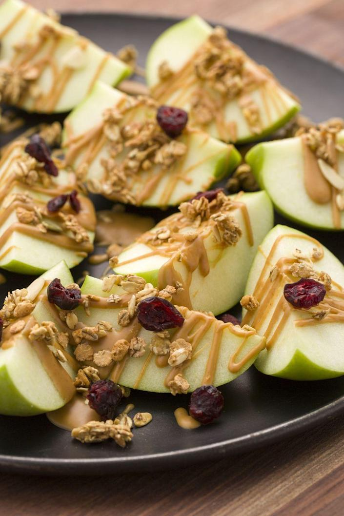"""<p>Drizzle apple nachos with warm peanut butter and top with granola and dried fruit for a dreamy healthy snack.</p><p>Get the recipe from <a href=""""https://www.delish.com/cooking/recipe-ideas/recipes/a45383/peanut-butter-apple-nachos-recipe/"""" rel=""""nofollow noopener"""" target=""""_blank"""" data-ylk=""""slk:Delish"""" class=""""link rapid-noclick-resp"""">Delish</a>.</p>"""