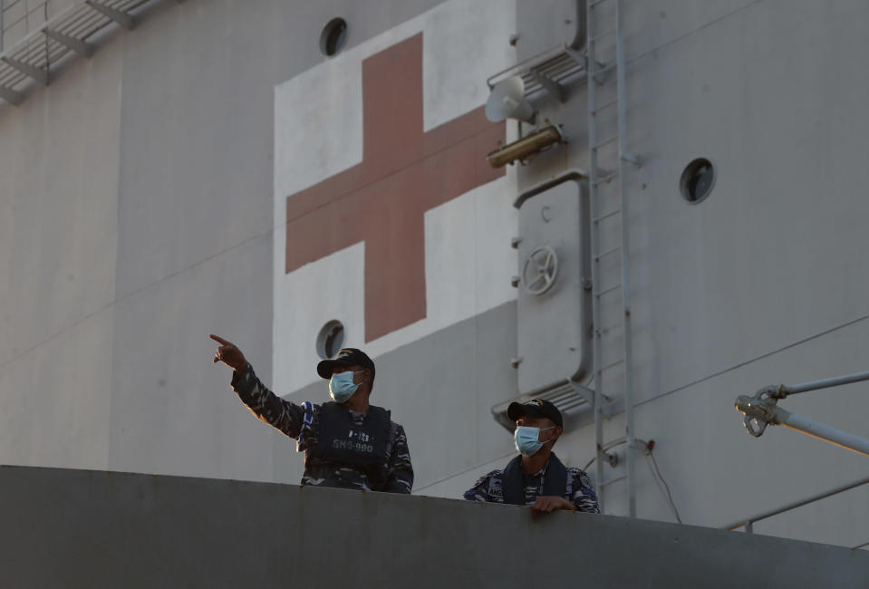 Members of Indonesian stand on its hospital ship KRI Dr. Soeharso as it prepares to join the search for submarine KRI Nanggala that went missing while participating in a training exercise, off Banyuwangi, East Java, Indonesia, Saturday, April 24, 2021. The Indonesian submarine went missing after its last reported dive Wednesday off the resort island, and concern is mounting it may have sunk too deep to reach or recover in time. (AP Photo/Achmad Ibrahim)