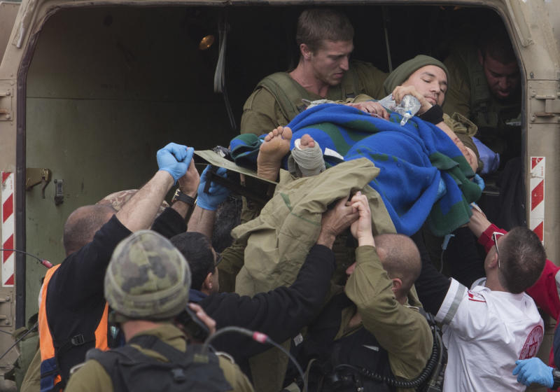 A wounded Israeli soldier is brought to a soccer field to be evacuated to a hospital, in the village of Masade in the Golan Heights, Tuesday, March 18, 2014. A roadside bomb hit an Israeli patrol near the frontier with the Golan Heights on Tuesday, the army said, wounding four soldiers in the most serious violence to strike the area since the Syrian conflict began three years ago. Israel said it responded with artillery strikes on Syrian army targets. Israel captured the Golan Heights from Syria in the 1967 Middle East war and later annexed the strategic area in a move that was not internationally recognized. (AP Photo/Jinipix) ****ISRAEL OUT***