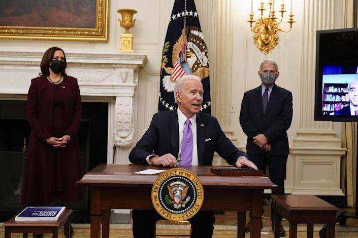 President Biden sits at a desk as Vice President Kamala Harris and Dr. Anthony Fauci stand behind him.