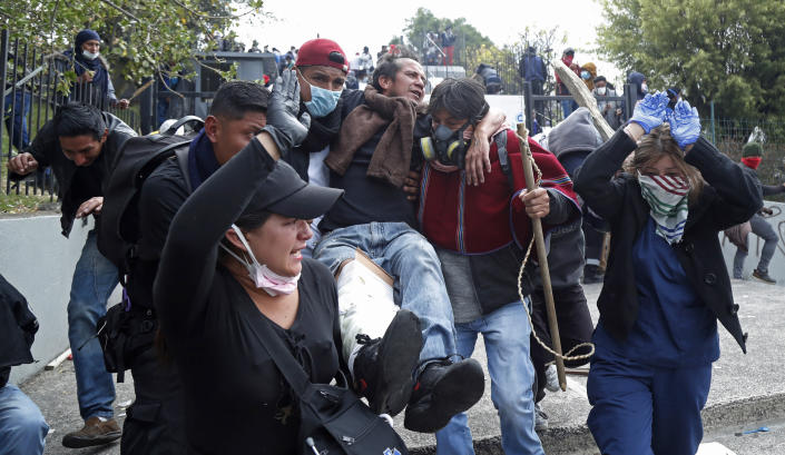 An injured anti-government protester is carried away during clashes with police near the National Assembly in Quito, Ecuador, Tuesday, Oct. 8, 2019. Anti-government protests, which began when President Lenín Moreno's decision to cut subsidies led to a sharp increase in fuel prices, has persisted for days, and clashes led the president to move his besieged administration out of Quito. (AP Photo/Dolores Ochoa)