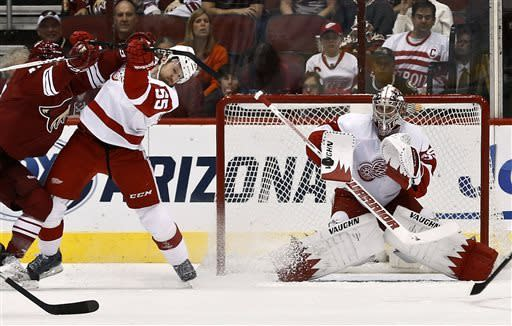 Detroit Red Wings' Jimmy Howard, right, makes a save as Red Wings' Niklas Kronwall (55), of Sweden, gets hit by Phoenix Coyotes' Chris Brown, left, in the first period of an NHL hockey game on Thursday, April 4, 2013, in Glendale, Ariz. (AP Photo/Ross D. Franklin)