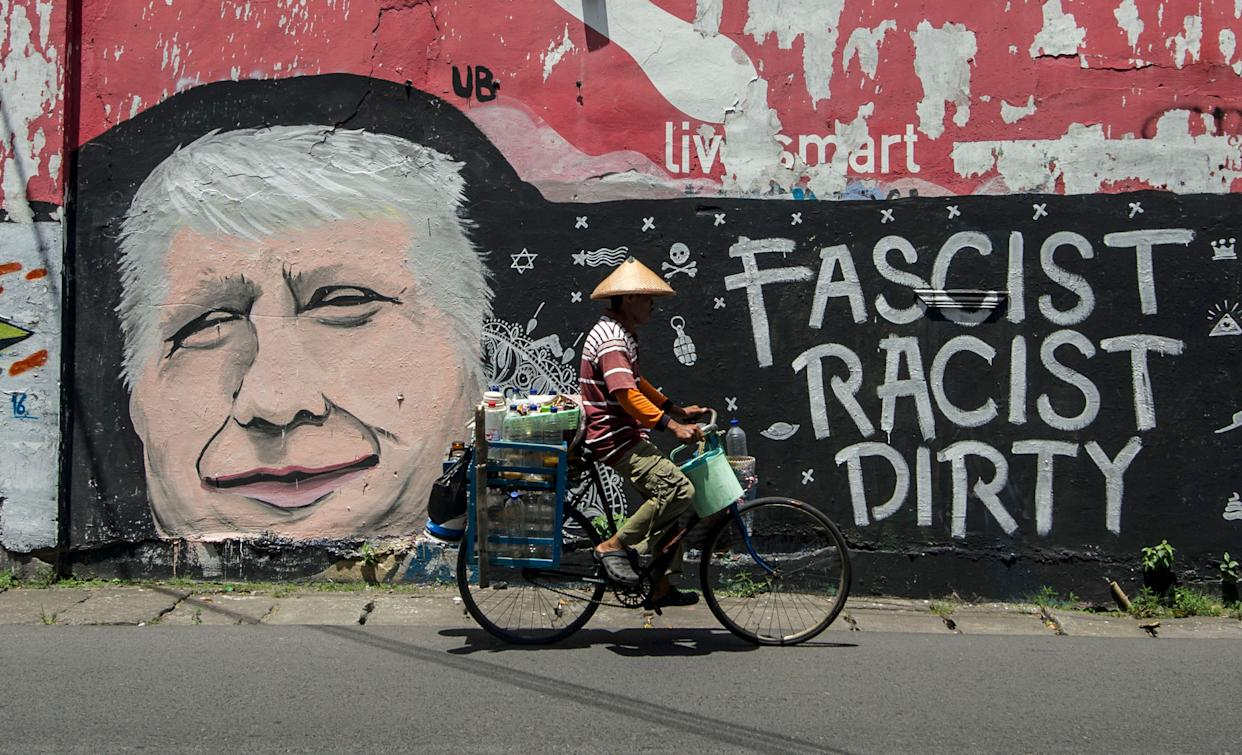 A man cycles past graffiti condemning US Republican presidential nominee Donald Trump, on a street in Surabaya, Indonesia's east Java on October 17, 2016.