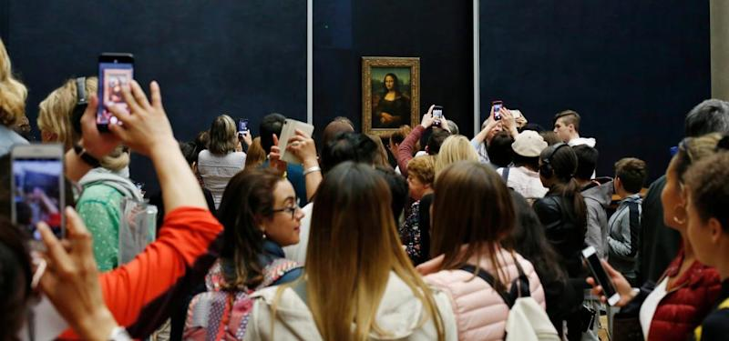 Smile, please … tourists take snaps of the Mona Lisa at the Louvre.