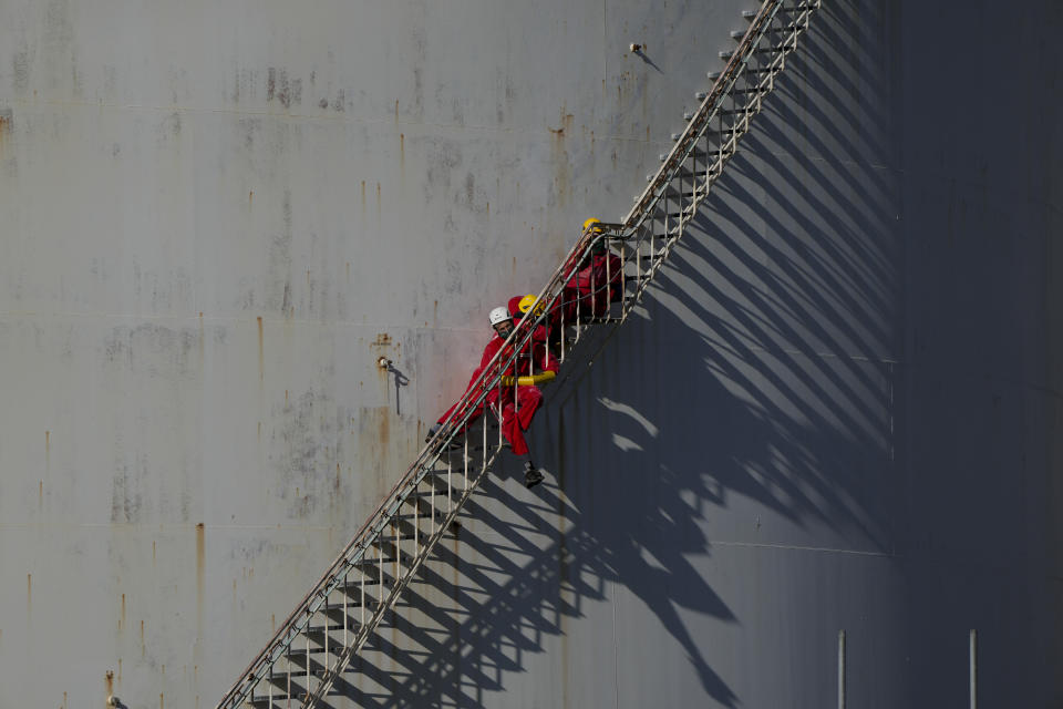 Greenpeace climate activists block the access on the staircase of a fuel storage tank as others stage a protest at a Shell refinery in Rotterdam, Netherlands, Monday, Oct. 4, 2021. A coalition of environmental groups launched a campaign calling for a Europe-wide ban on fossil fuel advertising ahead of the United Nations Climate Change Conference, also known as COP26, which start in Glasgow on Oct. 31st, 2021. (AP Photo/Peter Dejong)