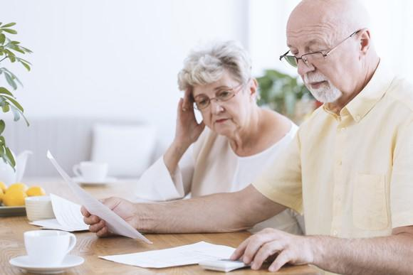 Serious senior couple looks at papers while the man uses a calculator