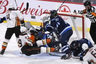 Anaheim Ducks' Devin Shore (29) falls to the ice as he scores on Winnipeg Jets goaltender Connor Hellebuyck (37) after a scramble for the puck during the third period of an NHL hockey game, Sunday, Dec. 8, 2019 in Winnipeg, Manitoba. (Fred Greenslade/The Canadian Press via AP)