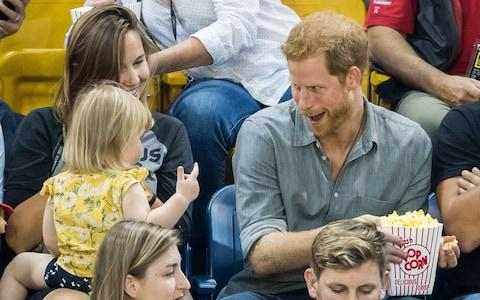 Prince Harry pulls his popcorn away from Emily - Credit: Samir Hussein/WireImage
