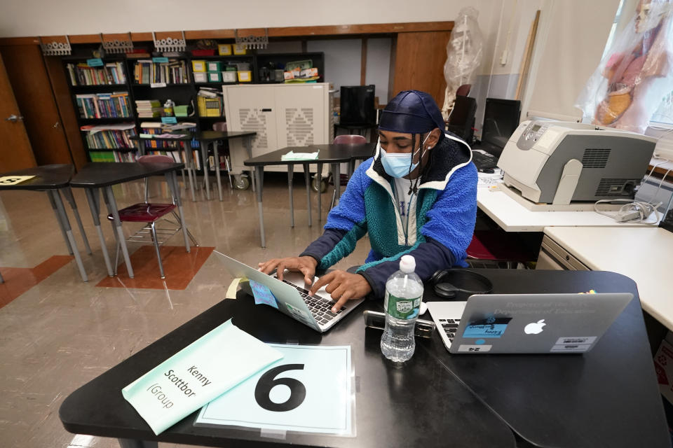 """Student Kenny Scottborough, 19, of the Bronx, works on a laptop in a science class at West Brooklyn Community High School, Thursday, Oct. 29, 2020, in New York. The high school is a """"transfer school,"""" catering to a students who haven't done well elsewhere, giving them a chance to graduate and succeed. The school reopened Monday after it was forced to shut down for three weeks due to a spike in coronavirus cases in the neighborhood. (AP Photo/Kathy Willens)"""