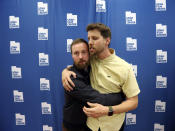 """In this May 3, 2019, photo, Aaron Ruell, who played the character Kip, left, and Jon Heder, who played Napoleon Dynamite, hug during a photo-op as they celebrate the 15th anniversary of the cult classic comedy """"Napoleon Dynamite,"""" in Salt Lake City. (AP Photo/Rick Bowmer)"""