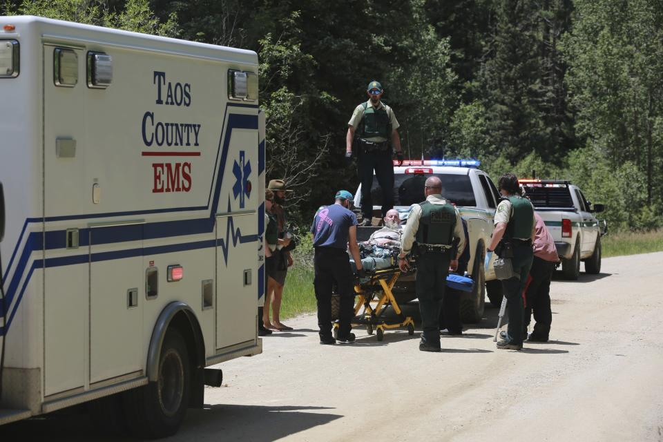Forest Service officers, county medical staff and Rainbow Gathering volunteers transfer an elderly patient from a pickup truck to an ambulance on Friday, July 2, 2021, in the Carson National Forest, outside of Taos, N.M. The condition of the man was not immediately known. He was flow out of the area by helicopter. (AP Photo/Cedar Attanasio)