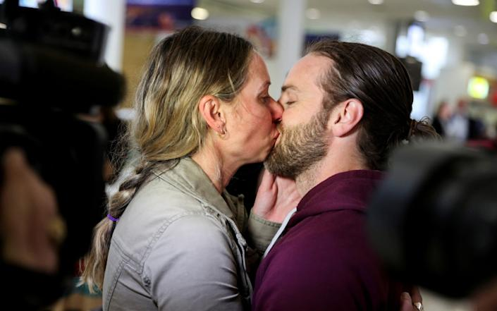 Adam Draper and his partner Stacey Brown kiss as she arrives from New Zealand after the Trans-Tasman travel bubble opened overnight - Reuters