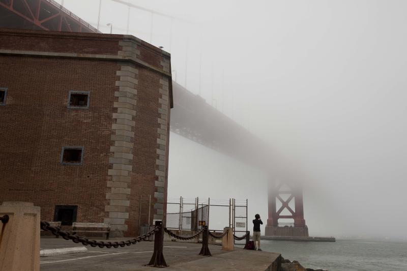 """In this photo taken Thursday, Sept. 27, 2012, a man stands beside Fort Point and looks out at the fog-covered Golden Gate Bridge in San Francisco. San Francisco has a long history as a favorite site for filmmakers and the movie buffs who want to see the spots where their favorite scenes took place, from Fort Point under the Golden Gate Bridge where Jimmy Stewart saved Kim Novak in """"Vertigo"""" to the steps of City Hall, where Sean Penn gave an impassioned speech in """"Milk,"""" to Alcatraz, stage for Clint Eastwood and many others. (AP Photo/Eric Risberg)"""